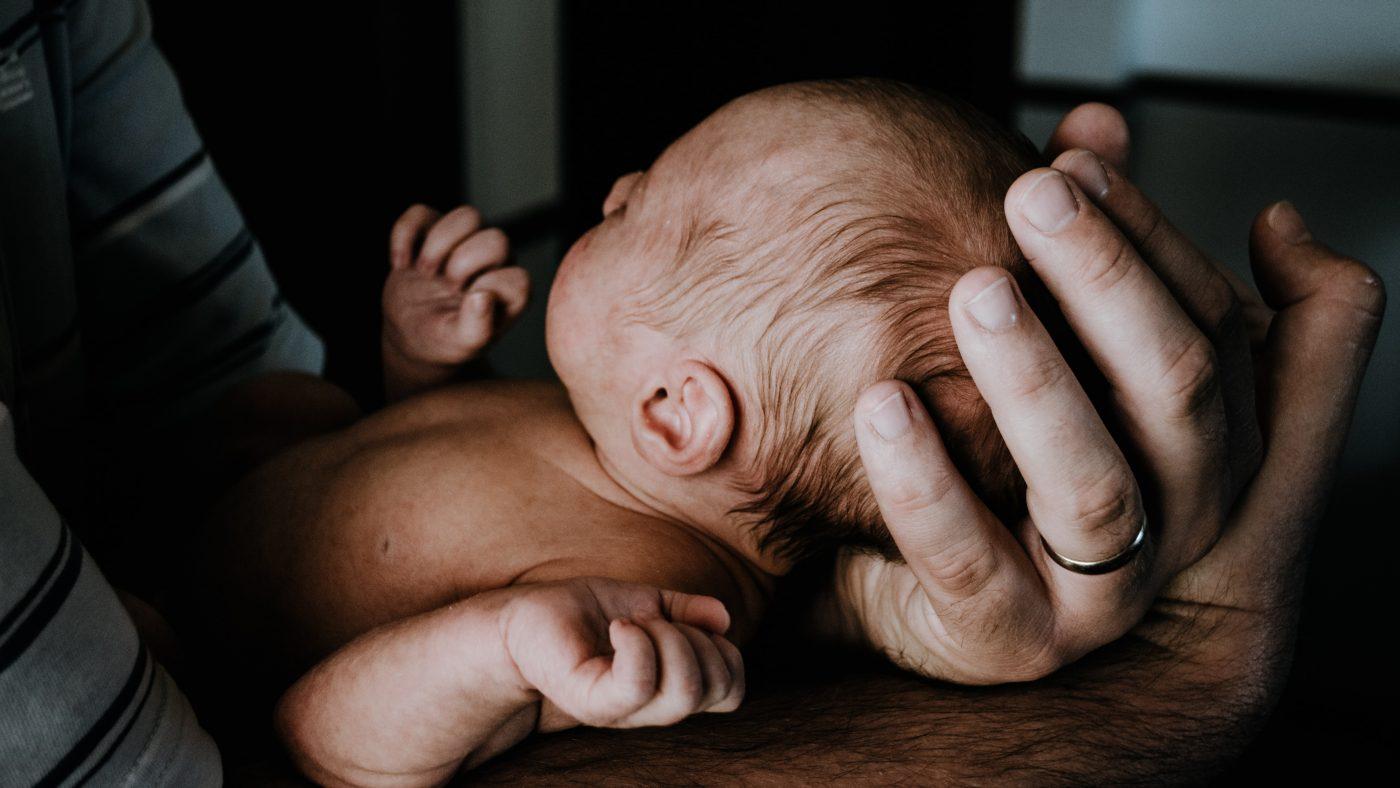 Mann mit neugeborenem Baby im Arm