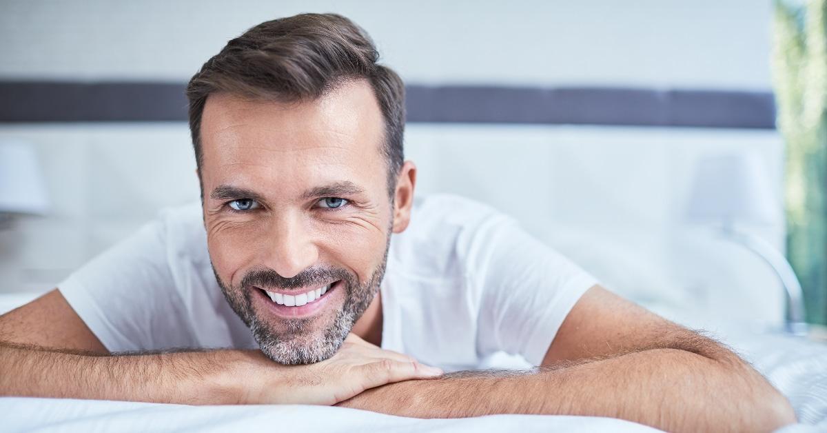 Entspannter, kraftvoller Mann der auf einem Bett liegt